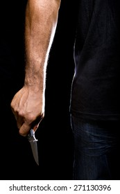 Close up of a robbers hands holding a knife in the shadows.  The man is a criminal holding a  weapon.