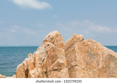 Close up rock with sea and clear sky in background.