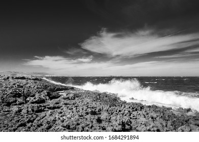 close up of a rocky beach in Qawra Point Beach in Malta on a cloudy day