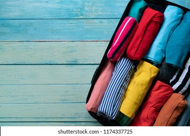 close up of rolled colorful clothes in a luggage for a new journey