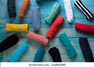 close up of rolled colorful clothes on wooden table background