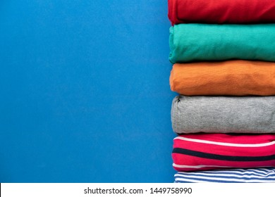 close up of rolled colorful clothes on blue background