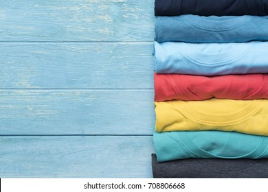 close up of rolled colorful clothes on wood table background