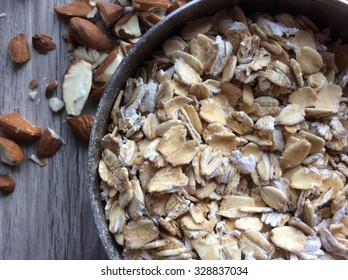 Close up of rolled oats in a measuring cup with chopped almonds on a wooden cutting board