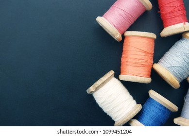Close up Rolls of Vintage Colorful Threads Needles. Clothes Repair, Blue Dark Background. Sewing Work Process.