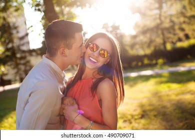 Close up romantic beauty portrait of happy hipster couple in love hugs and having fun, evening sunlight, stylish sunglasses, emotions, joy, youth, sunny colors, hugs and kisses.