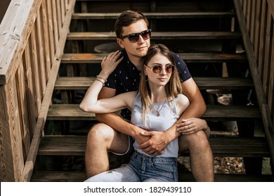 Close up of romantic couple in embrance look away on building background. Happy man and woman are sitting on wood stairs