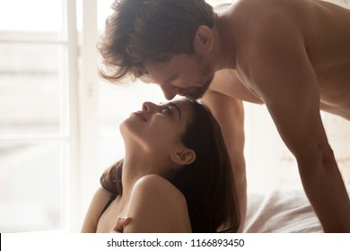 Close up of romantic couple looking in eyes during sensual foreplay in bedroom, loving boyfriend admire young girlfriend during prelude in bed, tender lovers facing each other enjoying intimate moment