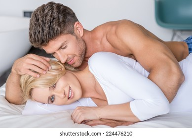 Close up Romantic Partners Lying on White Bed Fashion Shoot. Pretty Woman Looking at Camera While Handsome Partner Looking His Partner.