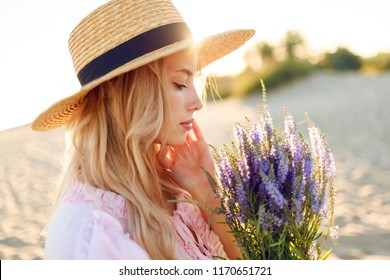 Close up romantic portrait of tender blonde young woman with bouquet of lavender . Sunset colors. Summer beach.  Perfect skin. Holiday and vacation mood.