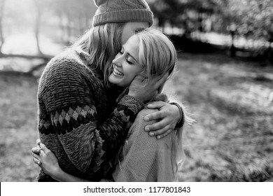 Close up romantic portrait of young hipster couple in love. Happy woman with man embracing and kissing in bright autumn park. Wearing sweater and knitted hat. Black and white.