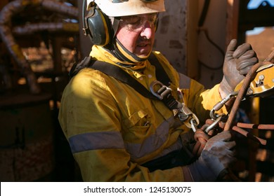 Close up rope access fitter technician abseiler working at height using safety device descending down after completed performing daily task maintenance repairs construction mine, Perth, Australia