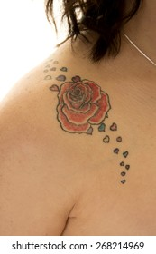 A close up of a rose tattoo on her bare shoulder.