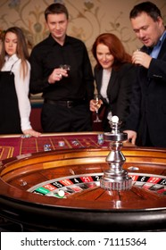 Close up of roulette table in casino with group of people on background