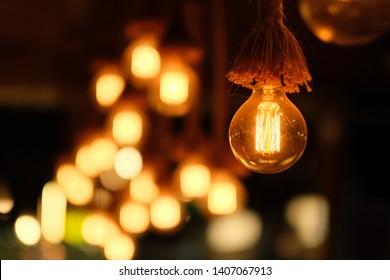 close up round dazzle bulb under tassel. Blur yellow lights in dark background