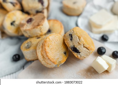 Close up of round shaped  blueberry scones styled with butter cubes and fresh blueberries, sweetened and glazed. The scones are typical component of traditional English afternoon tea.