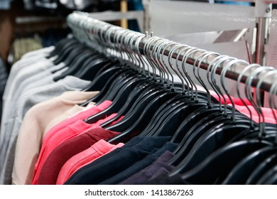 Close up of row of color sweater hanging on a metal rack in a department store