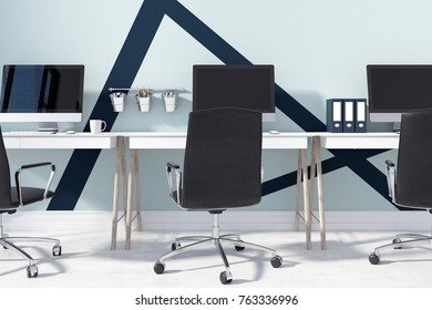 Close up of a row of computer screens on white and wooden tables in an open space office with pale blue and black walls. 3d rendering mock up
