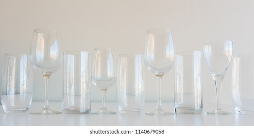 Close up of row of empty mismatched glassware arranged in pattern on shelf, including wine glasses and tumblers - drinking concept.