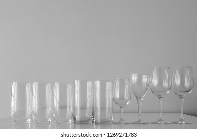 Close up of row of empty mismatched glassware arranged in height order on shelf, including wine glasses and tumblers - drinking concept (black and white)
