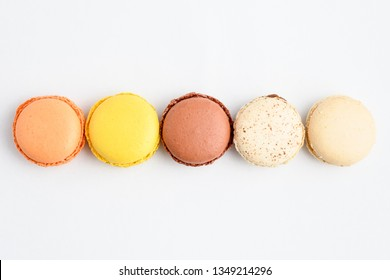 Close up of a row of five sweet French macarons with different aromas, isolated on white, flavours of orange,  lemon, caramel, chocolate, coconut and vanilla, pastel colors