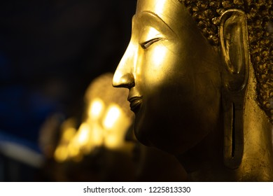 close up row of golden buddha statue in the light and shadow of sun at Wat Pra Sri Mahathat temple, Phitsanulok province, Thailand