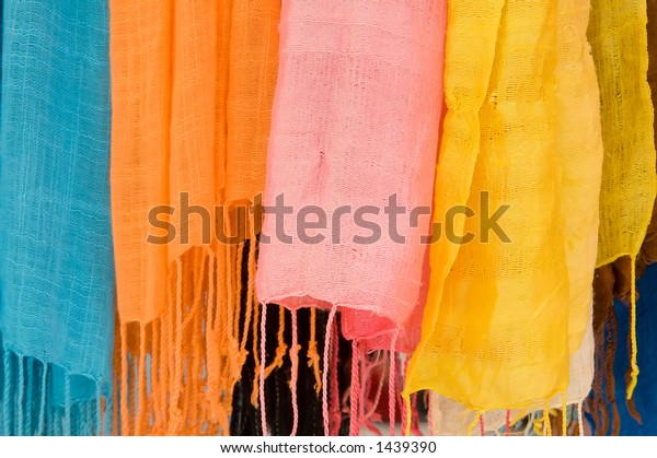 Close up of a row of scarfs in a market in tuscany