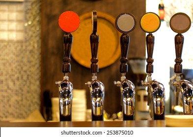 Close Up of Row of Shiny Beer Taps of Different Brews in Bar