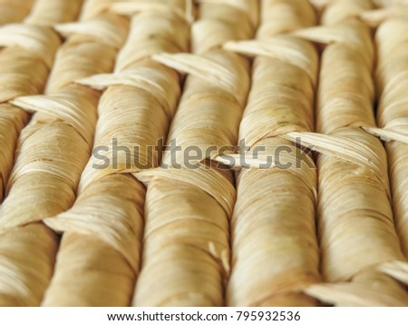 Close up rows of natural woven basketry showing detail of the woven pattern. Dried leaves are used to create the design. Background texture.