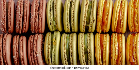Close up of rows of pistachio, almond and salted caramel macarons sitting on their sides