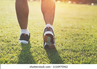 close up runer leg  running on grass with sunset at park