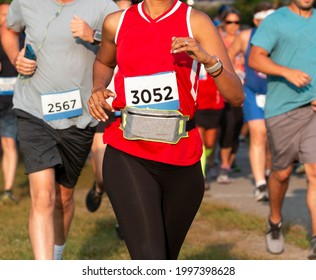 Close up of runners racing a 5K in a trail with a women wearing a fanny pack around her waist to carry her personal iteams.