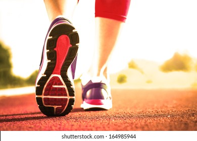 Close up of running shoes in use.Woman fitness sunrise jog workout welness concept