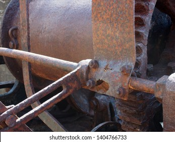 a close up of rusted cogs bolts and gears on an old broken industrial winching machine