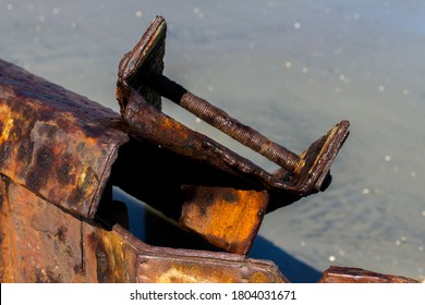 Close up of a rusted sea groin cover broken and bent backwards and extending into a pool of sea water on bright daylight