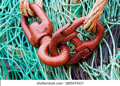 Close up of Rusted swivel with jaw connected to a  Mooring Boat Swivel Marine Anchor against green fishing nets.
