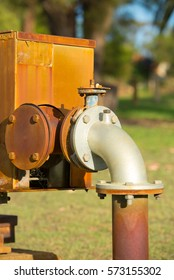 Close up rustic colored pump pipeline with elbow pipe and old valve for residential energy supply, blurred background outdoors and copy space.