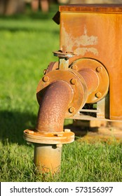 Close up rustic colored pump pipeline on grass with elbow pipe and old valve for residential energy supply, blurred background and copy space.