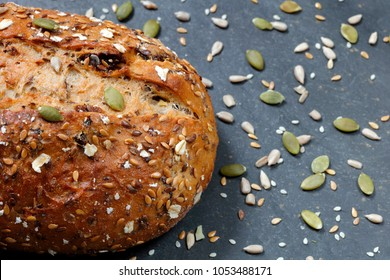 Close up of rustic whole grain bread loaf in baking tray on slate stone table top with scattered seeds