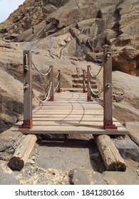 Close up of rustic wooden bridge in arid ravine with rock formations. Hanging structure of old wood to bridge the unevenness in dry ravine. Architecture and construction detail.