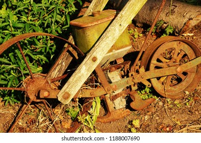 Close up of rusty old garden implement with sunshine lighting the wooden struts and green plants behind the implement