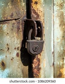 Close up of rusty padlock on old painted metal door