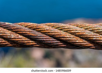 Close up of a rusty twisted steel wire rope cable, isolated in front of a blue sky and blurred rock and grass background.