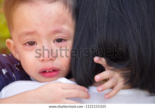 Close Up of Sad Little Asian Boy is Crying with tried on mother's shoulder.love and warm from mom console little heart from sad.