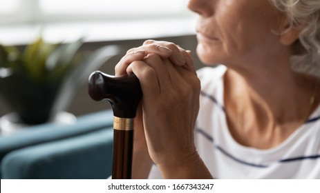 Close up of sad lonely old lady with walking stick lost in thoughts thinking and pondering at home, upset abandoned middle-aged 60s woman with cane feel distressed, elderly solitude concept