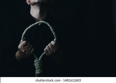 Close up of a sad man holding rope with hangman's noose in the dark room  while  making decision  to suicide herself with copy space