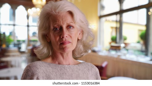 Close up of sad older woman standing in banquet hall or restaurant