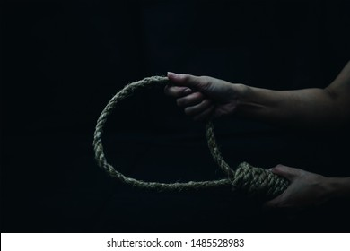 Close up of a sad person holding rope with hangman's noose in the dark room  while  making decision  to suicide herself with copy space