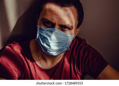 Schließen Sie traurig gedankenvolles Portrait von Erwachsenen in medizinischer Maske sitzen an Wand mit starren Augen. Bleiben Sie isoliert zu Hause. Quarantänekonzept. COVID-19 Pandemievirus. Soziale Trennung