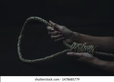 Close up of a sad woman holding rope with hangman's noose in the dark room  while  making decision  to suicide herself with copy space